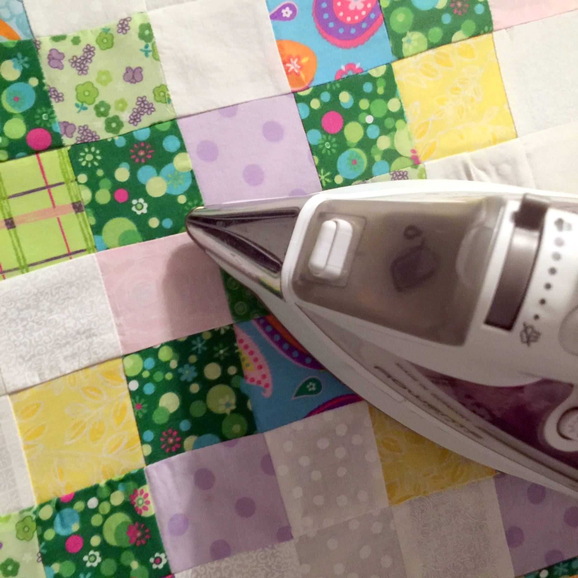 ironing an baby irish chain quilt in green pink purple blue and yellow