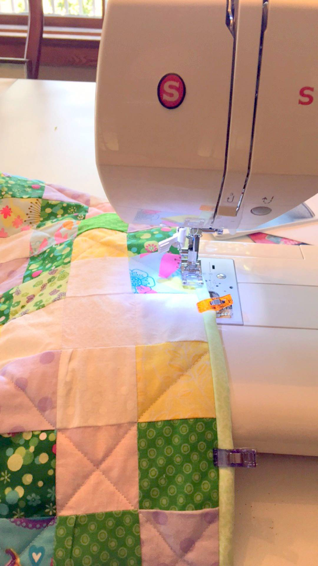 sewing the binding onto an irish chain baby quilt