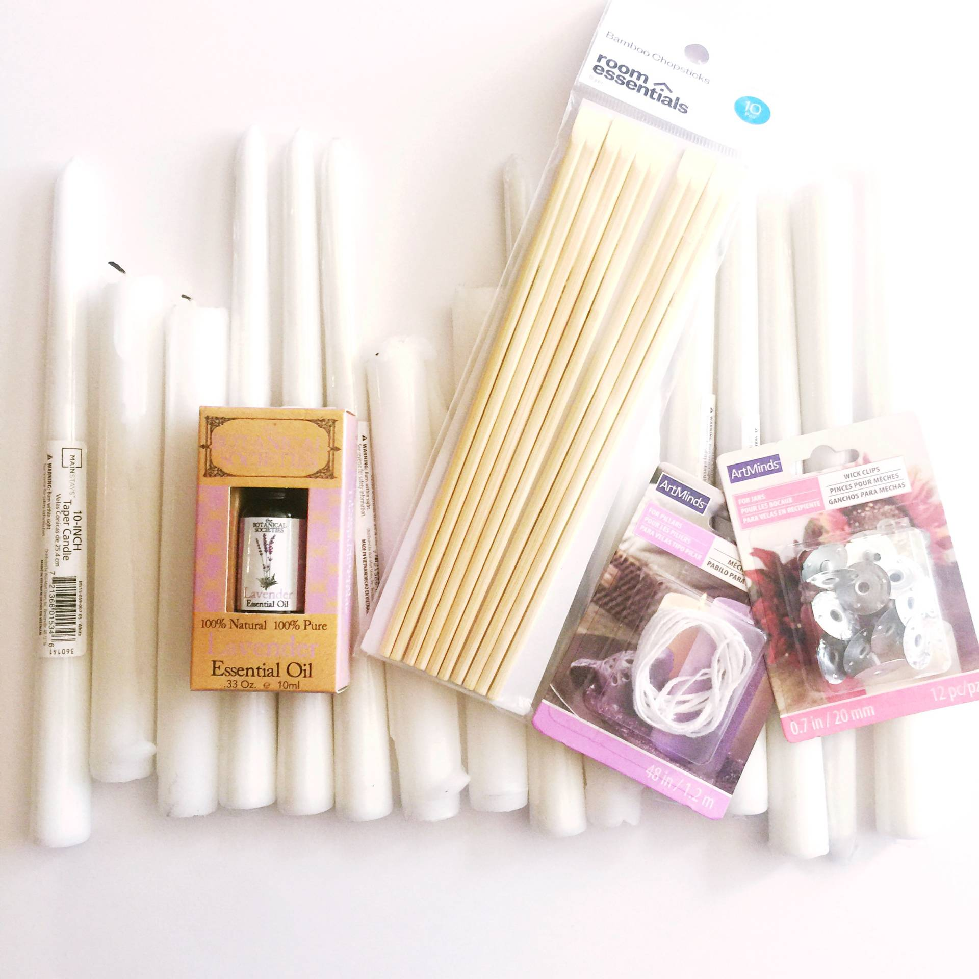 DIY candle making supplies: wicks, metal bases, essential oils, chopsticks, and wax